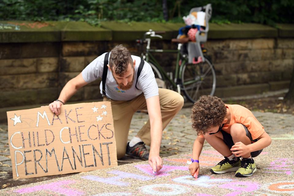 BROOKLYN, NEW YORK - JULY 12: Justin Ruben and Rime Leonard draw with chalk to celebrate new monthly Child Tax Credit payments and urge Congress to make them permanent. (Photo by Bryan Bedder/Getty Images for ParentsTogether)