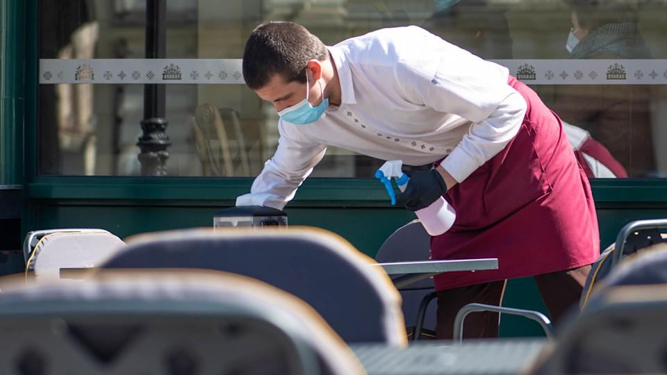 Vilnius, Lithuania - April 30 2020: Waiter with a mask disinfects the table of an outdoor bar, café or restaurant, reopen after quarantine restrictions.
