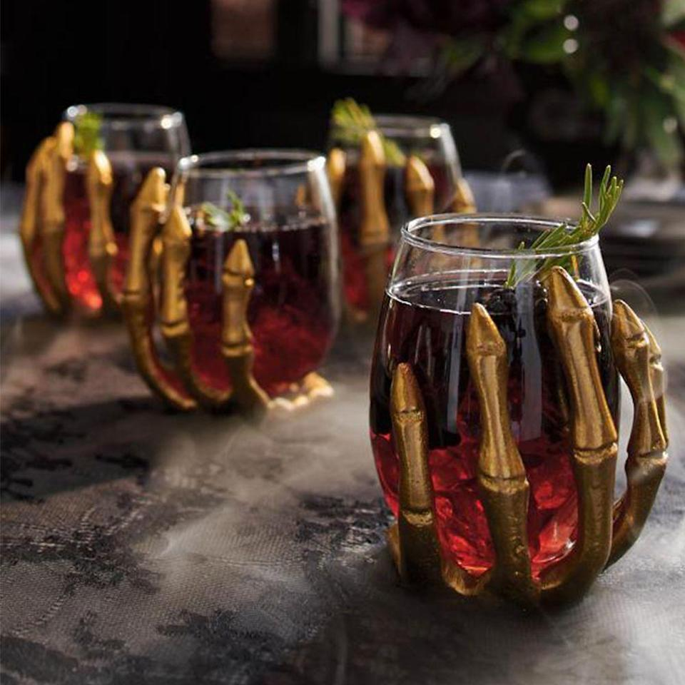 """<p>grandinroad.com</p><p><a href=""""https://go.redirectingat.com?id=74968X1596630&url=https%3A%2F%2Fwww.grandinroad.com%2Fskeleton-hand-wine-glasses-2c-set-of-four%2Fhalloween-haven%2Fnewest-additions%2F1471665&sref=https%3A%2F%2Fwww.bestproducts.com%2Flifestyle%2Fg36981907%2Fgrandin-road-halloween-decorations%2F"""" rel=""""nofollow noopener"""" target=""""_blank"""" data-ylk=""""slk:Shop Now"""" class=""""link rapid-noclick-resp"""">Shop Now</a></p><p>Your cabinet may already be stocked with wine glasses, but having ones that are wrapped with skeleton hands will make your next glass of vino especially spooky.</p><p><strong>More:</strong> <a href=""""https://www.bestproducts.com/home/decor/g33549584/chic-halloween-wine-glasses/"""" rel=""""nofollow noopener"""" target=""""_blank"""" data-ylk=""""slk:These Halloween-Themed Glasses Are a Must for Wine Drinkers"""" class=""""link rapid-noclick-resp"""">These Halloween-Themed Glasses Are a Must for Wine Drinkers</a></p>"""