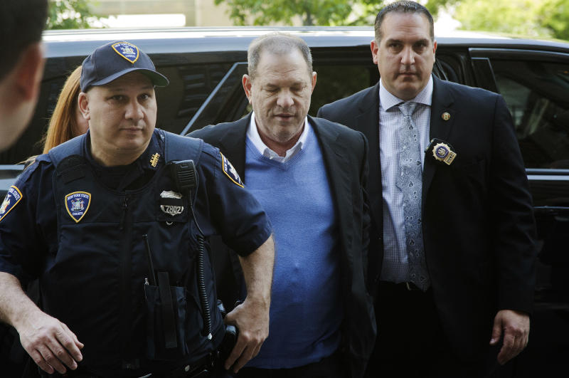 FILE- In this May 25, 2018 file photo, NYPD Detective Nicholas DiGaudio, right, escorts Harvey Weinstein into court in New York. New York prosecutors say the former lead police detective in the sexual assault investigation urged one of Weinstein's accusers to delete information from her phone before turning it over to prosecutors. On Oct. 11, prosecutors had abandoned part of their sexual assault case against Weinstein when evidence surfaced that DiGaudio instructed a witness to keep quiet when she raised doubts about another accuser's claim of sexual misconduct. (AP Photo/Mark Lennihan, File)