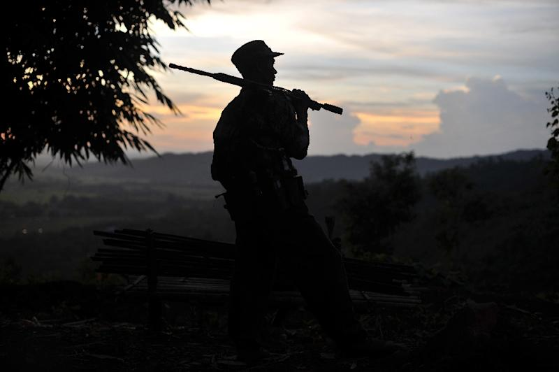 A Northern Burma (ABSDF-NB), an ally of the Kachin Independence Army (KIA) holding his weapon as he looks out from an outpost on the Laja Yang frontline, some 10 kilometres south of Laiza, a town in Myanmar's northern Kachin state (AFP Photo/Soe Than Win)