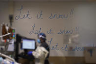 "A glass wall is decorated with the name of a Christmas song, ""Let it snow,"" as registered nurse Ashley Gould checks on a COVID-19 patient in an intensive care unit at Providence Holy Cross Medical Center in the Mission Hills section of Los Angeles, Tuesday, Dec. 22, 2020. (AP Photo/Jae C. Hong)"