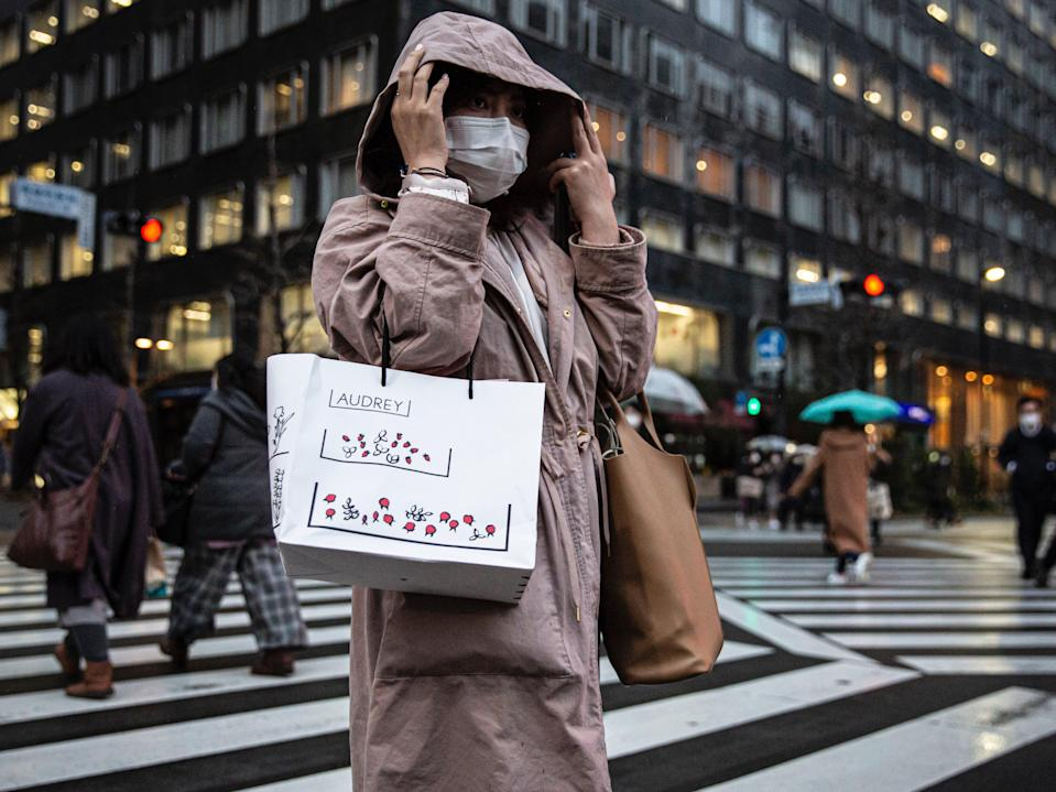 A woman wearing a face mask crosses a road on in Tokyo, Japan (Yuichi Yamazaki/Getty Images)