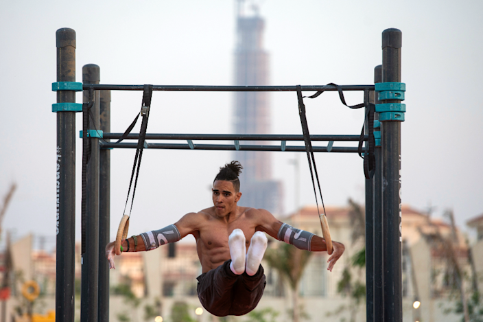 A male gymnast performs on the rings at the Street Workout in Cairo, Egypt - Friday 25 June 2021