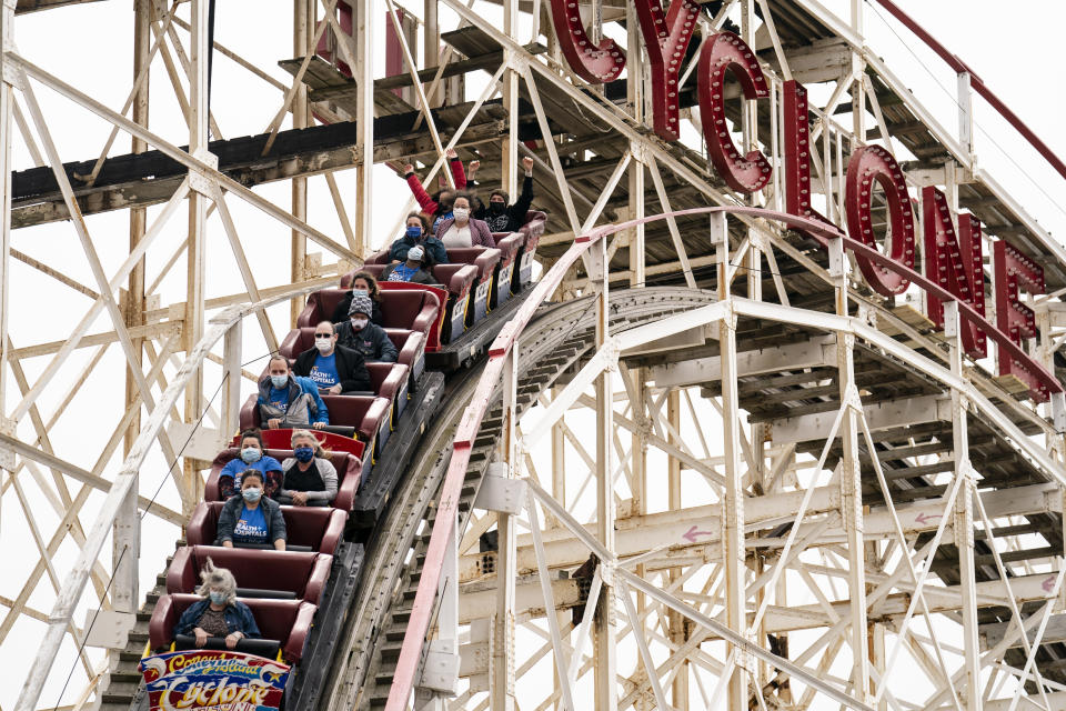 NYC Health+Hospital workers ride the Cyclone rollercoaster after the seasonal opening of the Coney Island amusement park area, Friday, April 9, 2021, in the Brooklyn borough of New York. Coney Island's illustrious amusement parks are reopening Friday after the coronavirus pandemic shuttered them all last year. (AP Photo/John Minchillo)
