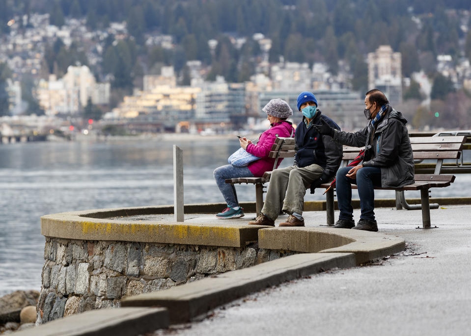 VANCOUVER, BRITISH COLUMBIA - JANUARY 04: Two man wearing protective face mask converse on a park bench along the seawall at Stanley Park on January 04, 2021 in Vancouver, Canada. The Provincial Health Officer (PHO) has ordered that events and gatherings be suspended and non-essential travel be avoided to reduce the transmission of COVID-19. (Photo by Andrew Chin/Getty Images)