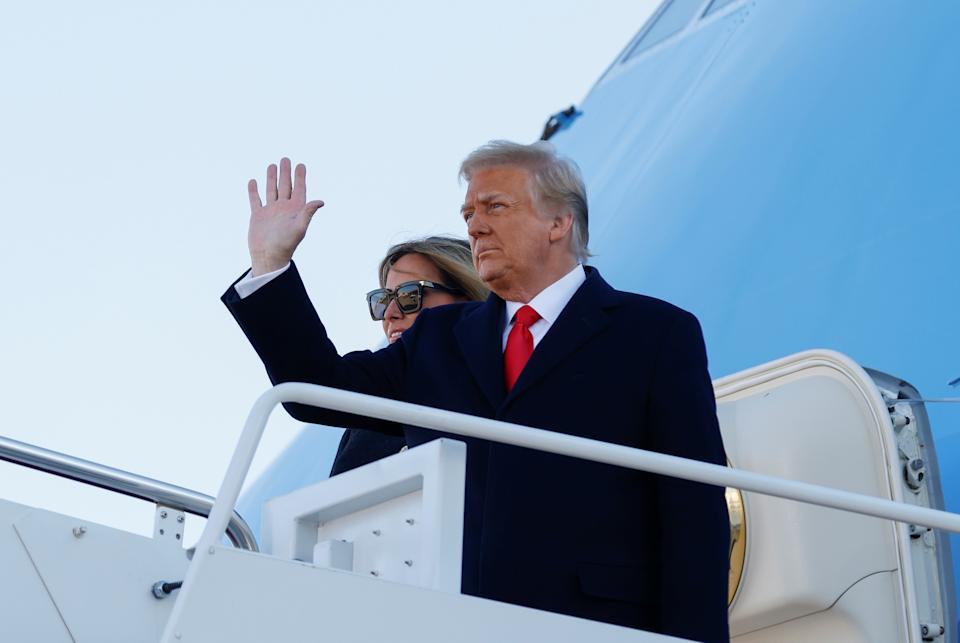 U.S. President Donald Trump, accompanied by first lady Melania Trump, waves as he boards Air Force One at Joint Base Andrews, Maryland, U.S., January 20, 2021. REUTERS/Carlos Barria