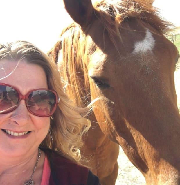 Michelle McKeaveney poses with one of the horses currently being used in equine-assisted therapy, which will be a part of the retreat.
