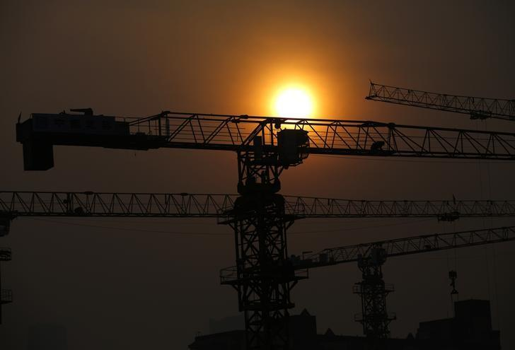 Cranes are silhouetted in front of the setting sun at a construction site for a new residential and commercial complex in Beijing