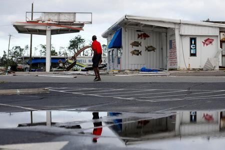 A man walks past a building damaged by Hurricane Michael in Panama City, Florida, U.S. October 11, 2018. REUTERS/Jonathan Bachman