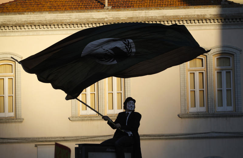 In this Saturday, Jan. 21, 2012, file photo, a protester wearing a Guy Fawkes mask waves a flag outside the Portuguese parliament during a demonstration against the government's austerity measures, in Lisbon. Austerity has been the main prescription across Europe for dealing with the continent's nearly 3-year-old debt crisis, brought on by too much government spending. Portugal is paying its bills only because of an international rescue loan. But the effect of lower government spending has been brutal: The economy is expected to contract 3.4 percent this year after a double-dip recession last year. (AP Photo/Francisco Seco)