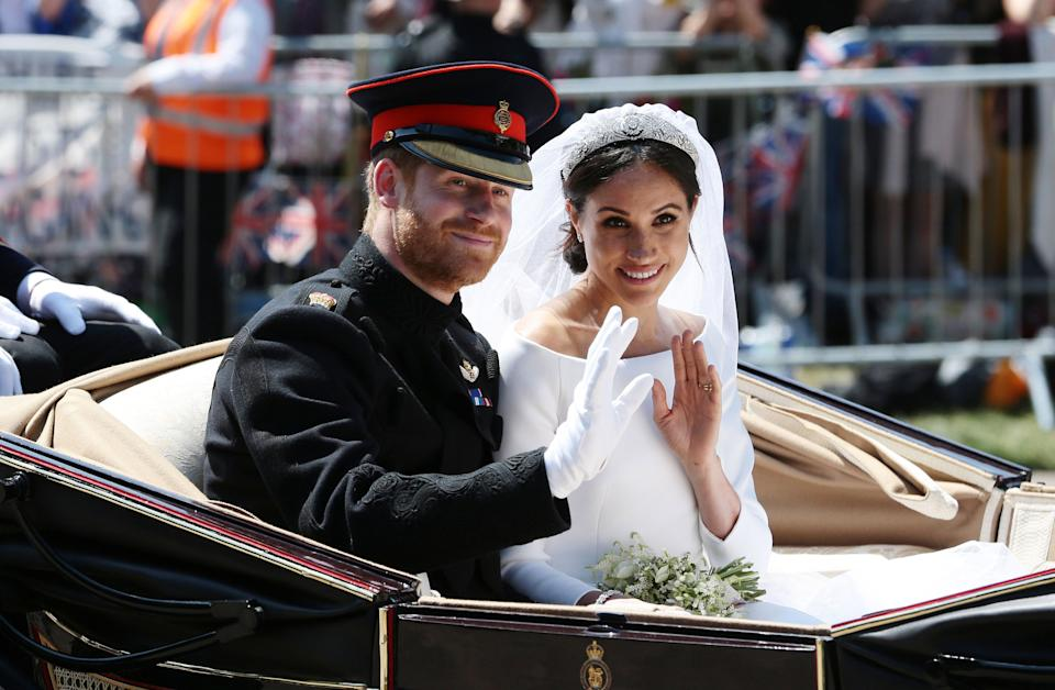 Prince Harry and Meghan Markle appear on their wedding day in an  open carriage