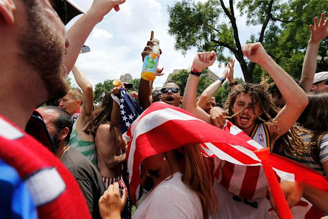 Soccer fans react at the end of the U.S-Germany 2014 World Cup soccer match, when the result of the Portugal-Ghana match put the U.S. through to the knockout stage of the tournament, at an outdoor viewing party in Dupont Circle in Washington June 26, 2014. REUTERS/Jonathan Ernst (UNITED STATES - Tags: SPORT SOCCER WORLD CUP)