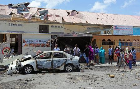 People gather at the scene of an explosion at the entrance of a cafe near the compounds housing government ministries in the Somali capital Mogadishu