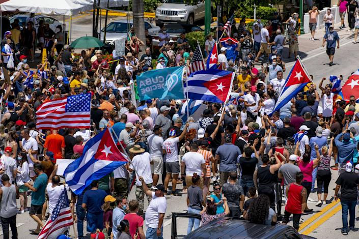 People march in the streets and wave Cuban flags during a protest in solidarity with thousands of Cubans who took to the streets in various locations in Cuba, in one of the largest protests to take place on the island, at Versailles Cuban restaurant off 8th Street in the Little Havana neighborhood of Miami, on Sunday, July 11, 2021. (Daniel A. Varela/Miami Herald via AP)