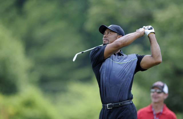 Tiger Woods watches his shot on the driving range during a practice round at the Quicken Loans National golf tournament, Tuesday, June 24, 2014, in Bethesda, Md. (AP Photo/Nick Wass)