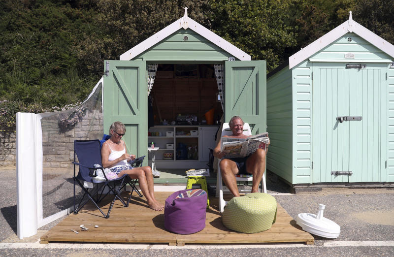 Rob and Sally Underhill sit outside their beach hut on a sunny day, in Bournemouth, England, Wednesday, May 20, 2020. Lockdown restrictions due to the coronavirus outbreak have been relaxed allowing unlimited outdoor exercise and activities such as sunbathing. (Andrew Matthews/PA  via AP)