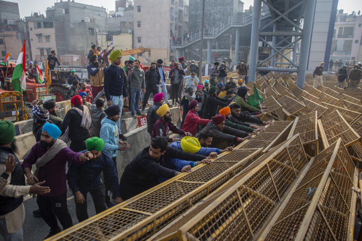 Protesting farmers break police barricades as they march to the capital during India's Republic Day celebrations in New Delhi, India, Tuesday, Jan. 26, 2021. Tens of thousands of farmers drove a convoy of tractors into the Indian capital as the nation celebrated Republic Day on Tuesday in the backdrop of agricultural protests that have grown into a rebellion and rattled the government. (AP Photo/Altaf Qadri)