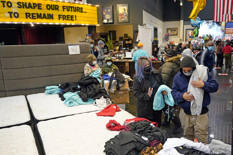 People select shirts and sweatshirts being given away at a Gallery Furniture store after the owner opened his business as a shelter for those without power at their homes Tuesday, Feb. 16, 2021, in Houston. More than 4 million people in Texas still had no power a full day after historic snowfall and single-digit temperatures created a surge of demand for electricity to warm up homes unaccustomed to such extreme lows, buckling the state's power grid and causing widespread blackouts. (AP Photo/David J. Phillip)