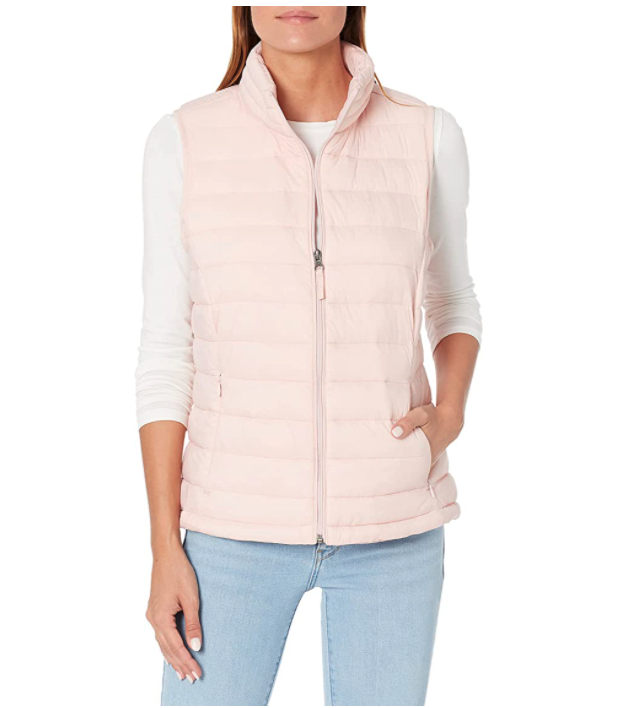 Model wears Amazon Essentials Womens Lightweight Water-Resistant Packable Puffer Vest in light pink with jeans. Image via Amazon.