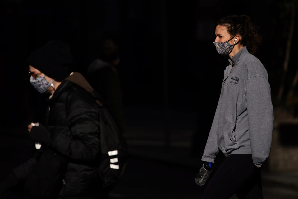 In this Nov. 18, 2020 photo, people wearing face masks cross Broad Street in Philadelphia. As governors and mayors grapple with an out-of-control pandemic, they are ratcheting up mask mandates and imposing restrictions on small indoor gatherings, which have been blamed for accelerating the spread of the coronavirus. (AP Photo/Matt Slocum)