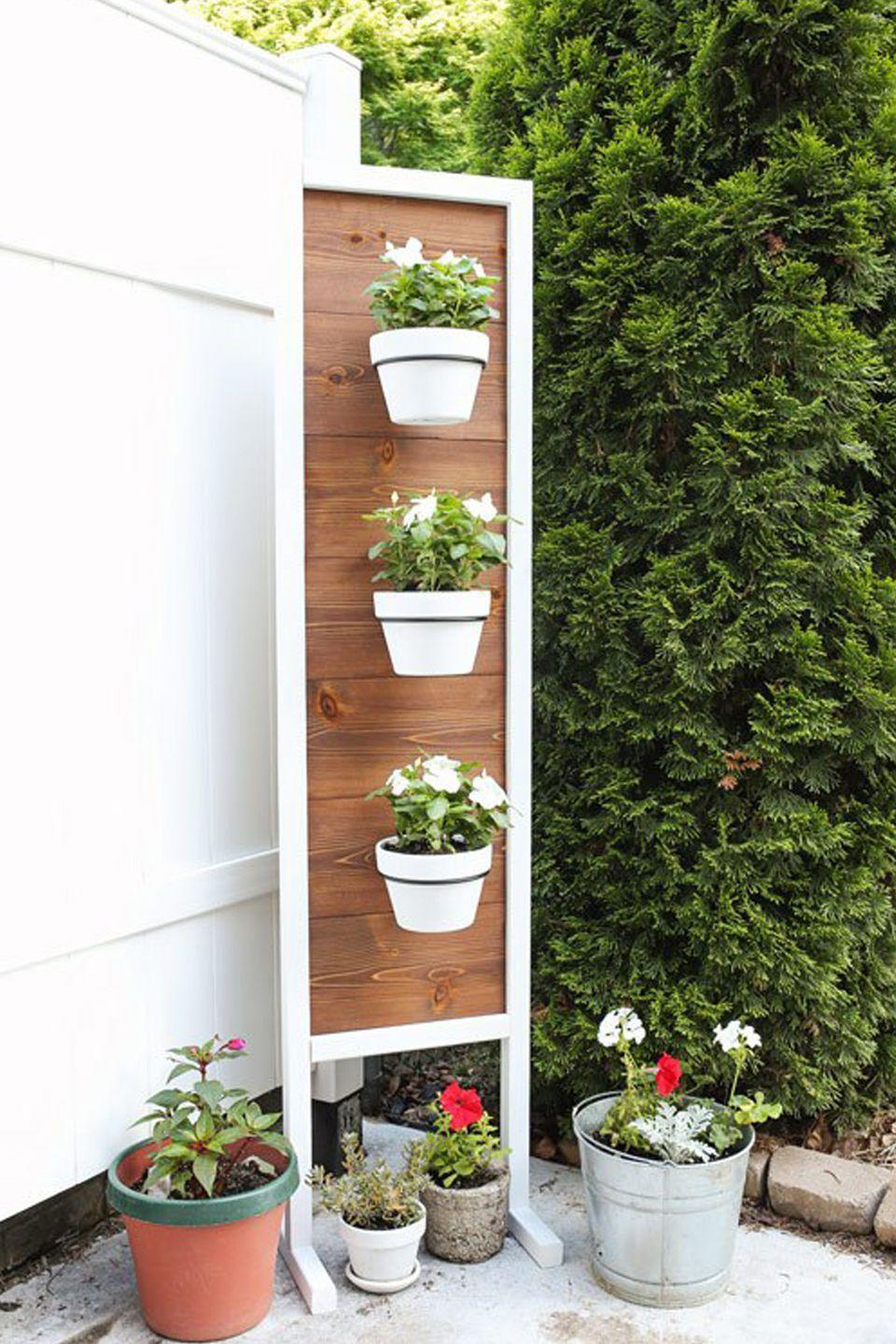 """<p>Not only does this DIY take up less surface area than multiple pots on the ground would, but it can also serve as a privacy fence for nosy neighbors. </p><p><em><a href=""""https://angelamariemade.com/2017/06/diy-vertical-planter-stand/"""" rel=""""nofollow noopener"""" target=""""_blank"""" data-ylk=""""slk:Get the tutorial at Angela Marie Made »"""" class=""""link rapid-noclick-resp"""">Get the tutorial at Angela Marie Made »</a></em></p>"""