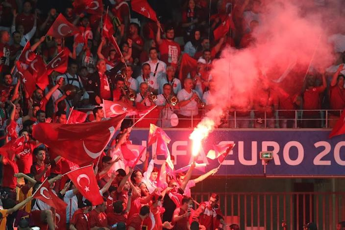 Turkey supporters wave the national flag and a flare during the Euro 2016 match between Spain and Turkey in Nice on June 17, 2016 (AFP Photo/Valery Hache)