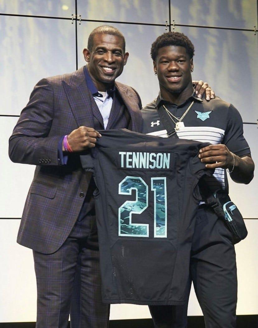 """NFL superstar """"Neon"""" Deion Sanders, left, presents Rockledge High football star Ladarius Tennison with his No. 21 jersey for the Under Armour All-Star Game in Orlando."""