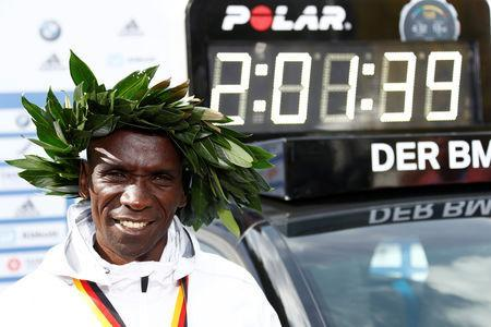 FILE PHOTO: Athletics - Berlin Marathon - Berlin, Germany - September 16, 2018 Kenya's Eliud Kipchoge celebrates after winning the Berlin Marathon alongside a clock showing his World Record breaking time REUTERS/Fabrizio Bensch
