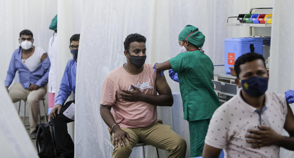 Medical workers administer vaccinations in India.