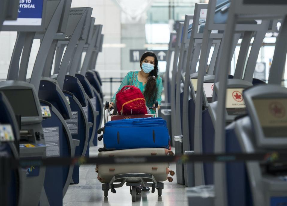 A woman wearing a face mask and pushing a full luggage cart walks between Air Canada kiosks