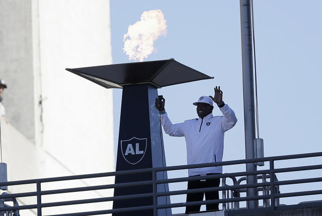 FILE - In this Nov. 4, 2012, file photo former Oakland Raiders wide receiver Cliff Branch lights a ceremonial torch for former Raiders owner Al Davis before an NFL football game between the Oakland Raiders and the Tampa Bay Buccaneers in Oakland, Calif. Branch, one of the Raiders' career-leading receivers who won three Super Bowls, has died. He was 71. (AP Photo/Marcio Jose Sanchez, File)