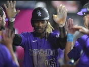 Colorado Rockies' Raimel Tapia is congratulated after scoring during the seventh inning of the team's baseball game against the Los Angeles Angels on Wednesday, July 28, 2021, in Anaheim, Calif. (AP Photo/John McCoy)