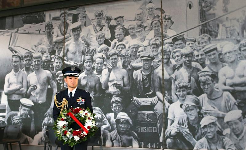 A Japanese naval officer holds a wreath in front of a photo of Australian World War II sailors at the Royal Australian Navy Heritage Centre in Sydney on November 22, 2015 (AFP Photo/David Moir)