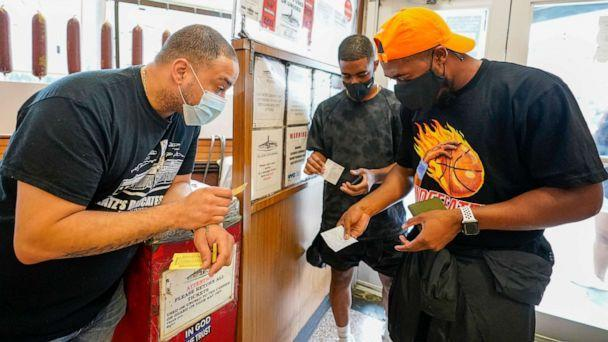 PHOTO: A Katz's Deli employee checks the proof of vaccination from customers who want to eat inside the restaurant, Aug. 17, 2021, in New York. (Mary Altaffer/AP)