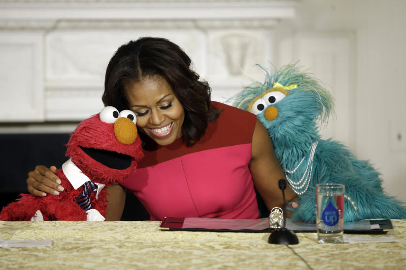 First lady Michelle Obama, center, with PBS Sesame Street's characters Elmo, left, and Rosita, right, as they help promote fresh fruit and vegetable consumption to kids in an event in the State Dining Room of the White House in Washington, Wednesday, Oct. 30, 2013. Sesame Workshop and the Produce Marketing Association (PMA) joined in Partnership for a Healthier America (PHA) in announcing a 2-year agreement to making healthy choices by using the Sesame Street characters to help deliver the messages about fresh fruits and vegetables. (AP Photo/Pablo Martinez Monsivais)