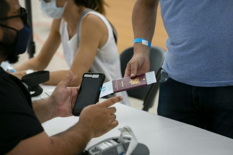 A man gives his passport for registration to get Johnson & Johnson Covid-19 vaccine at a pop-up vaccination center at the beach, in South Beach, Florida, on May 9, 2021