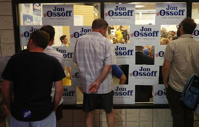 <p>People look through a window to watch as Democratic candidate Jon Ossoff speaks to volunteers and supporters on the last night before election day as he runs for Georgia's 6th Congressional District on June 19, 2017 in Roswell, Ga. (Photo: Joe Raedle/Getty Images) </p>