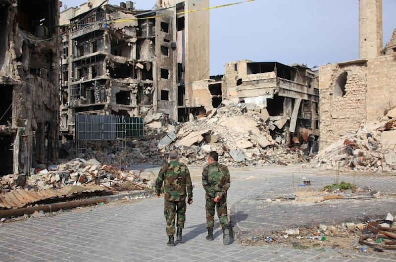 Syrian government forces walk on a heavily damaged street in the regime-controlled side of the northern city of Aleppo on November 9, 2015