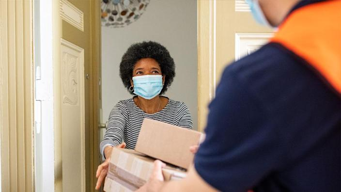 A stock photo of a woman receiving the delivery at her door
