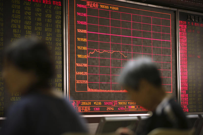Chinese investors monitor stock prices at a brokerage house in Beijing, Friday, Aug. 2, 2019. Asian stock markets plunged Friday after President Donald Trump's surprise threat of tariff hikes on additional Chinese imports. (AP Photo/Mark Schiefelbein)