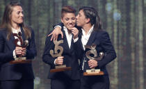 Manuela Giugliano, center, reacts after winning the trophy for best Italian Serie A women player, during the Gran Gala' soccer awards ceremony, in Milan, Italy, Monday, Dec. 2, 2019. (AP Photo/Antonio Calanni)