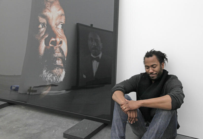 In this photo taken, Friday, April 6, 2012, artist Rashid Johnson poses with some of his work that is part of his first solo exhibition at the Museum of Contemporary Art in Chicago. In the last year, the Chicago native whose works made from everyday objects explore his own life story as well as larger issues of black identity, has garnered high-profile attention and awards from the art world. (AP Photo/M. Spencer Green)