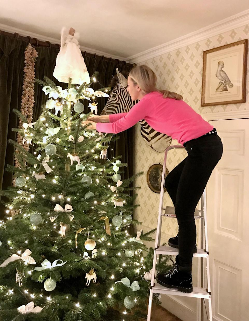 Adding the final touches to our tree. This lovely angel comes out every year.