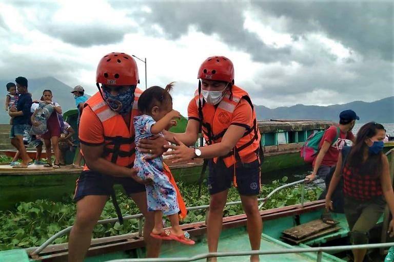Coastguard workers evacuate residents from the coastal villages of Buhi town, Camarines Sur province, south of Manila