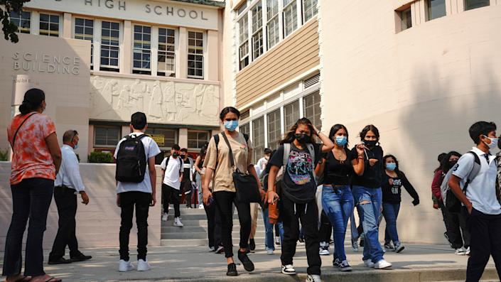 Students wearing face masks walk in a courtyard near the front of a high school building.