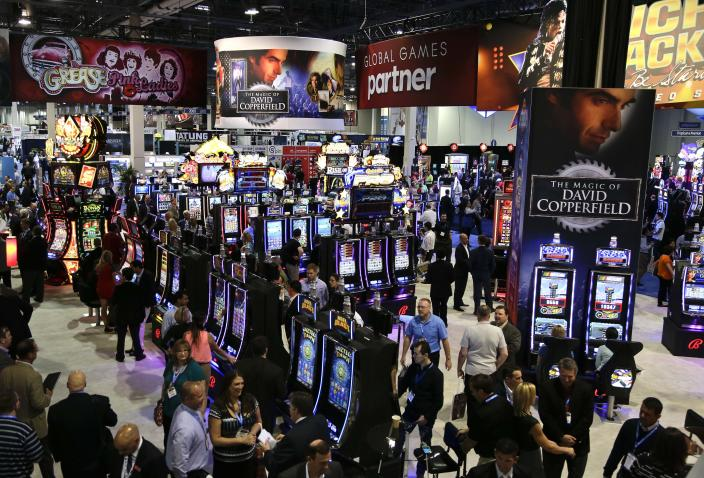 Gaming industry representatives meander through rows of slot machines at the Global Gaming Expo, Wednesday, Sept. 25, 2013, in Las Vegas. In addition to moving away from moving parts to video technology, the slot machine is undergoing a generational shift, and manufacturers are rolling out the first generation of joystick-controlled, penny arcade-themed gambling machines. (AP Photo/Julie Jacobson)
