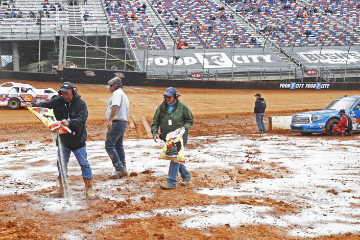 Safety workers spread drying agent before heat races for a NASCAR Truck Series race on Saturday, March 27, 2021, in Bristol, Tenn. (AP Photo/Wade Payne)