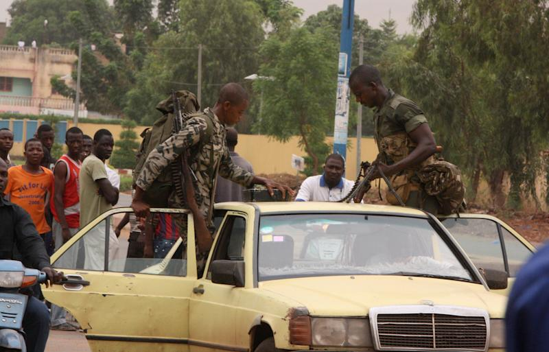 Two soldiers loyal to junta chief Capt. Amadou Sanogo load their weapons, including a machine gun, onto a taxi which they hailed while returning on foot from the parachutists military camp, where junta soldiers took control in fighting against anti-junta forces, in Bamako, Mali, Tuesday, May 1, 2012. Gunfire echoed across the capital Tuesday as Malian government troops battled each other, killing at least 12 people as one side tried to oust soldiers who seized power in a coup over a month ago. Mali's coup leaders, who ostensibly handed over power to an interim civilian government on April 12 but who still wield power, said they control the state broadcaster, the airport and a military base, fending off attacks by opposing forces. Sanogo told a private radio station Monday night that the countercoup had failed and that his soldiers have captured foreign fighters.(AP Photo/Harouna Traore)