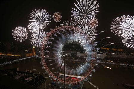 Fireworks explode across a London skyline near the London Eye during New Year celebrations in London January 1, 2014. REUTERS/Olivia Harris